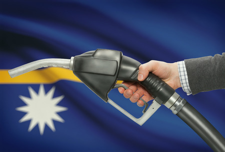 petrochemistry: Fuel pump nozzle in hand with flag on background - Nauru Stock Photo