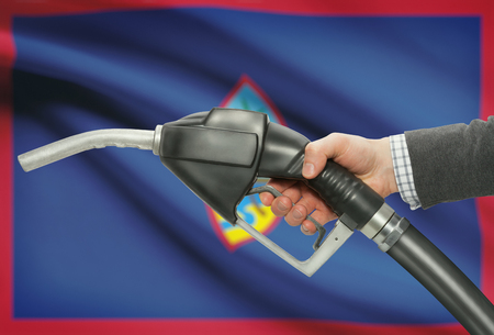 guam: Fuel pump nozzle in hand with flag on background - Guam
