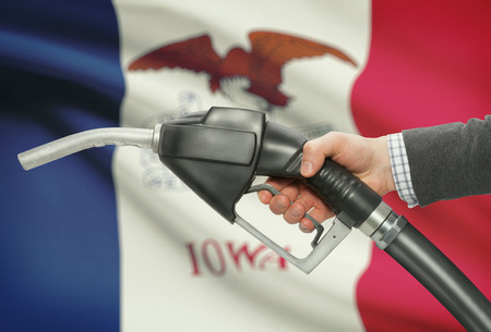 Fuel pump nozzle in hand with US states flags on background - Iowa