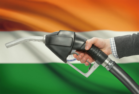 petrochemistry: Fuel pump nozzle in hand with flag on background - India Stock Photo