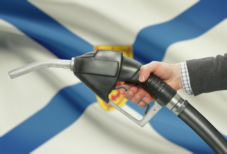 petrochemistry: Fuel pump nozzle in hand with Canadian territories and provinces flags on background - Nova Scotia Stock Photo