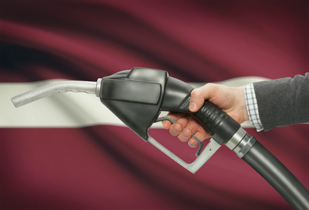 petrochemistry: Fuel pump nozzle in hand with flag on background - Latvia Stock Photo