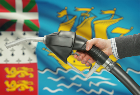 petrochemistry: Fuel pump nozzle in hand with flag on background - Saint Pierre and Miquelon Stock Photo