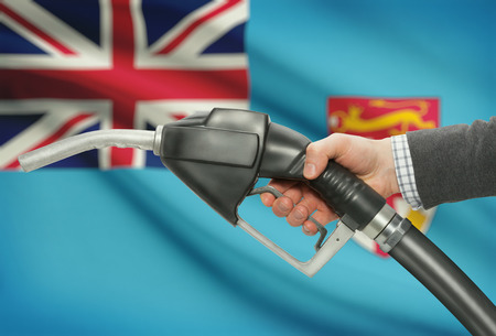 Fuel pump nozzle in hand with flag on background - Fiji Stock Photo