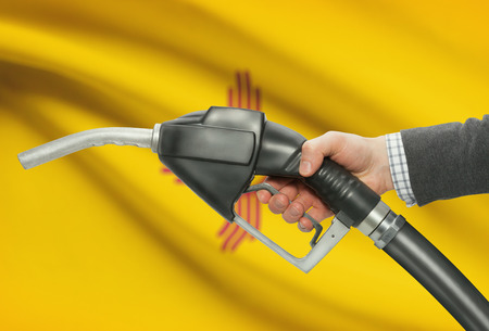 Fuel pump nozzle in hand with US states flags on background - New Mexico Stock Photo
