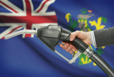 petrochemistry: Fuel pump nozzle in hand with flag on background - Pitcairn Islands
