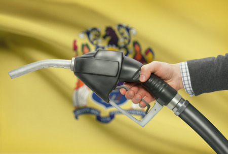 methanol: Fuel pump nozzle in hand with US states flags on background - New Jersey