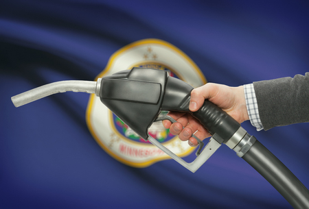 Fuel pump nozzle in hand with US states flags on background - Minnesota