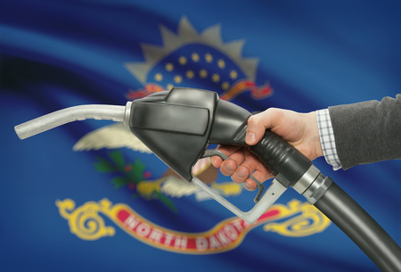 methanol: Fuel pump nozzle in hand with US states flags on background - North Dakota