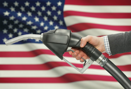 petrochemistry: Fuel pump nozzle in hand with flag on background - United States - USA Stock Photo