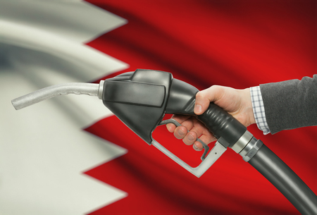 methanol: Fuel pump nozzle in hand with flag on background - Bahrain
