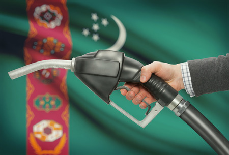 Fuel pump nozzle in hand with flag on background - Turkmenistan Stock Photo