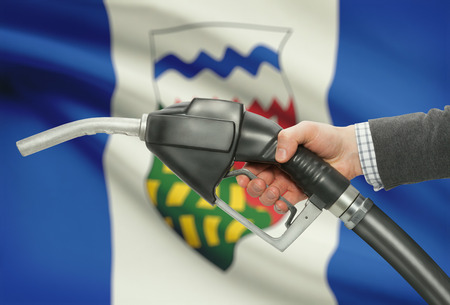 petrochemistry: Fuel pump nozzle in hand with Canadian territories and provinces flags on background - Northwest Territories