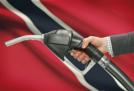 petrochemistry: Fuel pump nozzle in hand with flag on background - Trinidad and Tobago