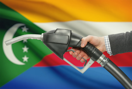 Fuel pump nozzle in hand with flag on background - Comoros