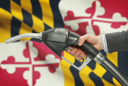 methanol: Fuel pump nozzle in hand with US states flags on background - Maryland