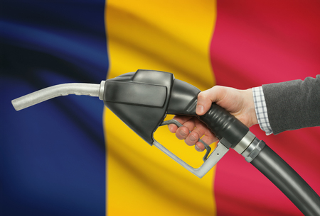 chadian: Fuel pump nozzle in hand with flag on background - Chad