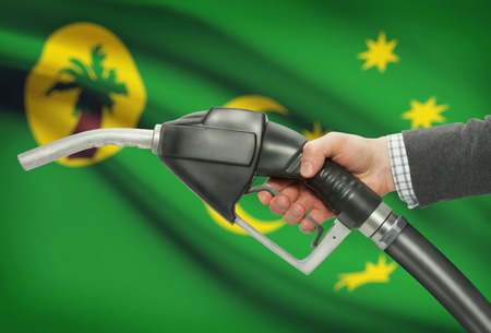 Fuel pump nozzle in hand with flag on background - Cocos (Keeling) Islands Stock Photo
