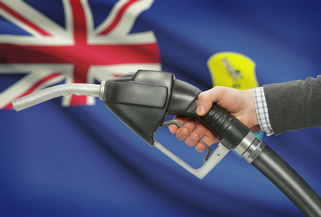 petrochemistry: Fuel pump nozzle in hand with flag on background - Saint Helena