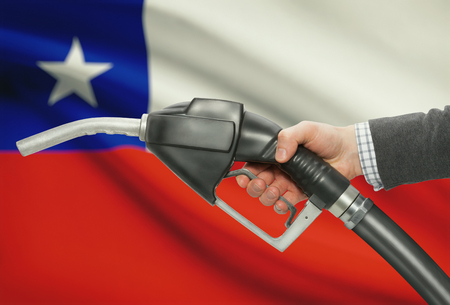 methanol: Fuel pump nozzle in hand with flag on background - Chile Stock Photo