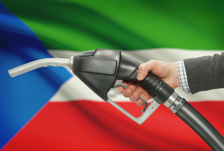 petrochemistry: Fuel pump nozzle in hand with flag on background - Equatorial Guinea Stock Photo