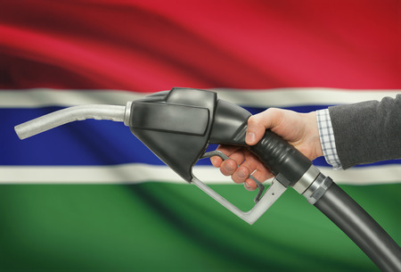 petrochemistry: Fuel pump nozzle in hand with flag on background - Gambia