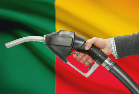 petrochemistry: Fuel pump nozzle in hand with flag on background - Benin
