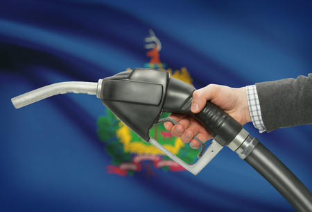 Fuel pump nozzle in hand with US states flags on background - Vermont