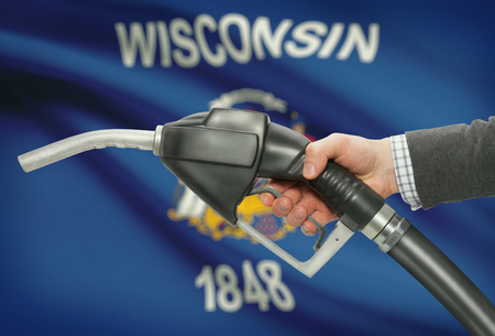 methanol: Fuel pump nozzle in hand with US states flags on background - Wisconsin
