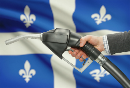 methanol: Fuel pump nozzle in hand with Canadian territories and provinces flags on background - Quebec