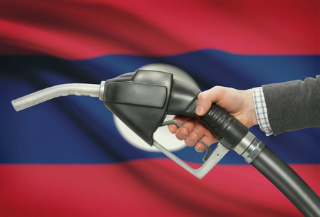 Fuel pump nozzle in hand with flag on background - Laos Stock Photo