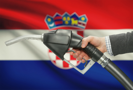 petrochemistry: Fuel pump nozzle in hand with flag on background - Croatia