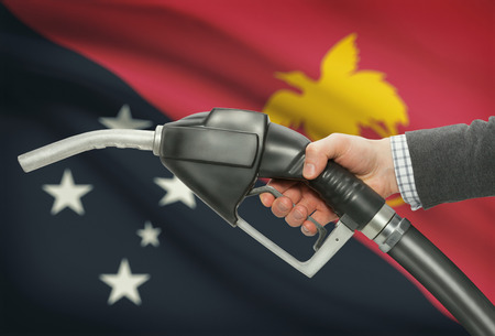 petrochemistry: Fuel pump nozzle in hand with flag on background - Papua New Guinea