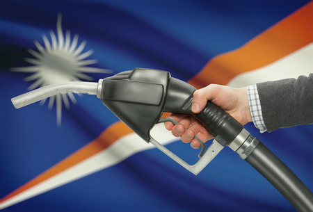 methanol: Fuel pump nozzle in hand with flag on background - Marshall Islands Stock Photo