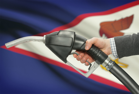 Fuel pump nozzle in hand with flag on background - American Samoa