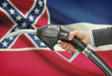 petrochemistry: Fuel pump nozzle in hand with US states flags on background - Mississippi