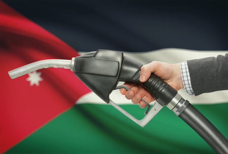petrochemistry: Fuel pump nozzle in hand with flag on background - Jordan