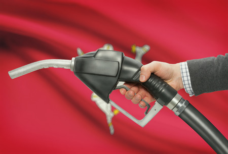 petrochemistry: Fuel pump nozzle in hand with flag on background - Isle of Man Stock Photo