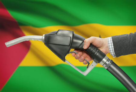principe: boquilla de la bomba de gasolina en la mano con la bandera en el fondo - Santo Tomé y Príncipe