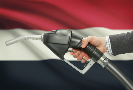 methanol: Fuel pump nozzle in hand with flag on background - Yemen