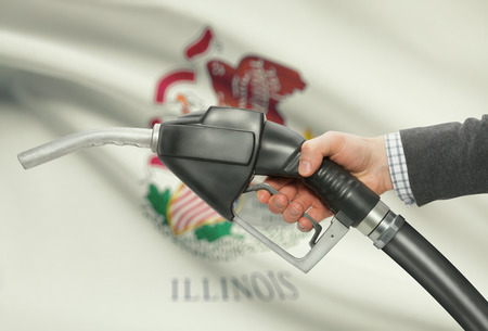 Fuel pump nozzle in hand with US states flags on background - Illinois Stock Photo