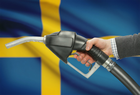 petrochemistry: Fuel pump nozzle in hand with flag on background - Sweden