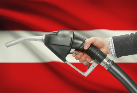 petrochemistry: Fuel pump nozzle in hand with flag on background - Austria Stock Photo