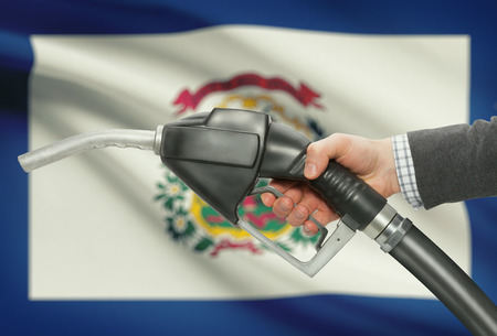 petrochemistry: Fuel pump nozzle in hand with US states flags on background - West Virginia Stock Photo