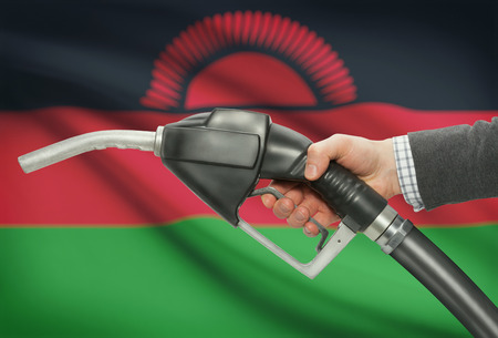 malawian flag: Fuel pump nozzle in hand with flag on background - Malawi