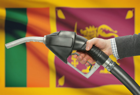 sri lankan flag: Fuel pump nozzle in hand with flag on background - Sri Lanka