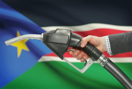 petrochemistry: Fuel pump nozzle in hand with flag on background - South Sudan