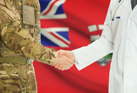 american hero: Soldier in uniform and doctor shaking hands with Canadian provincies and territories flags on background - Manitoba
