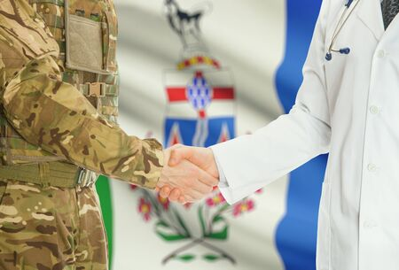 american hero: Soldier in uniform and doctor shaking hands with Canadian provincies and territories flags on background - Yukon