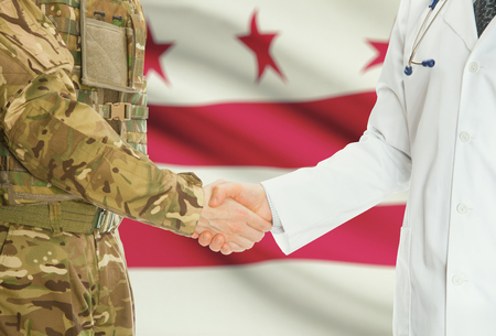 district columbia: Soldier in uniform and doctor shaking hands with US states flags on background - District of Columbia
